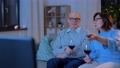 happy senior couple drink red wine and watch tv 65108630