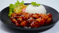 Dakgangjeong Fried Chicken with Spicy and Sweet Sauce  Sprinkle Sesame Served Rice Traditional Korean Food Crispy Chicken Style on Black Plate Decorate Vegetables sideview 65242961