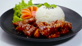 Dwaegangjeong Fried Pork with Spicy and Sweet Sauce Sprinkle Sesame Served Rice Traditional Korean Food Crispy pork Style on Black Plate Decorate Vegetables sideview 65242962
