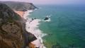 Praia da Adraga surfing beach. White atlantic ocean waves rolling towards sandy beach with tourists. Sintra, Portugal 65308025