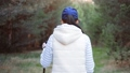 Rear view sports woman during nordic walk at forest. Medium shot on RED camera 65440077