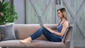 Attractive casual busy girl work on notebook at cozy rustic living room. FullHD Dragon RED camera 65450299