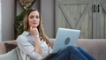 Portrait of female freelancer posing with laptop on couch. Medium close up shot on FullHD RED camera 65451023