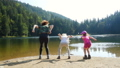 kids jumping and enjoying  on a forest lake 65453916