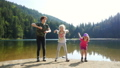 kids jumping and enjoying  on a forest lake 2 65453917