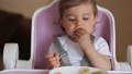 Beautiful little baby girl first time eating exotic fruits in high chair. Cute baby girl taste delitious fruist, mango, kiwi, and babana 65480554