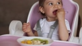 Beautiful little baby girl first time eating exotic fruits in high chair. Cute baby girl taste delitious fruist, mango, kiwi, and babana 65480556