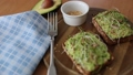 Defocused Toast with microgreens and guacamole on top. Rye toasted bread on wooden board. Healthy food at home. Vegan food concept. Camera motion 65481482