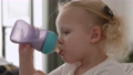 Toddler girl drinking milk from the bottle 65601464