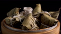 Cooking rice dumpling zongzi - Steamed Chinese food in a steamer, fresh prepared food for Dragon Boat Duanwu Festival isolated on black background, close up lifestyle. 65662190