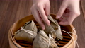 Eating rice dumpling zongzi - Young girl is eating fresh Chinese food at home on dark wooden table for Dragon Boat Festival, Duanwu Festival celebration. 65662194
