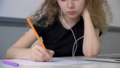 Curly girl teenager listening music in earphones and writing by pencil on paper sheet. School girl 65671421