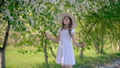 Young girl enjoying flowering fruit garden at sunny spring day. Happy girl in white dress and hat 65671443