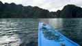 Bangka Boat Island hopping tour POV approaching bay of Kayangan Lake, Coron, Palawan, Philippines of a partially cloudy day. 60fps UHD H.264 65781090