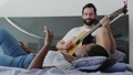 13 Man Playing Guitar And Woman Singing Song In Bedroom 65850742