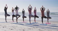 Multi-ethnic group of women doing yoga position on the beach and blue sky background 66089651