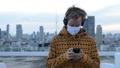 Young man in hoodie using phone while listening to music with mask against view of the city 66259085