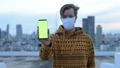 Young man with mask showing phone against view of the city 66259087