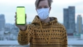 Face of young man with mask showing phone against view of the city 66259091