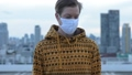 Face of young man with mask thinking against view of the city 66259096