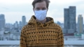 Face of young man with mask for protection from corona virus outbreak against view of the city 66259101