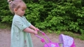 Little girl walking with her stroller toy in summer park 66363009