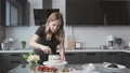 Professional chef is cooking cake. Young attractive housewife uses metal spatula and rotating table to aligns white cream on chocolate cake 66396421