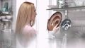 The young woman is looking at the ceramic plate at the store 66406010