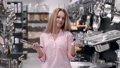 The pretty woman is holding up a grater and culinary tongs at the store 66406013
