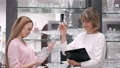 The woman is choosing glassware with a sales assistant a the tableware store 66406016