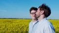 Two young guys in love admire each other in the field 66415702