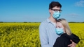 Young couple hugging in a field in protective masks 66415712
