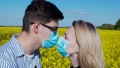 Young guy kisses a girl in a field through a mask 66415732
