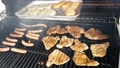 Slow motion of gas grill with pork and chicken marinated sliced steaks, sausages and cheeses grilling on flames. 66521702