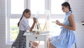 Mom and daughter paint at home in front of the window on easels and looked into the frame 66583061