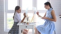 Mom and daughter paint at home in front of the window on easels 66583062