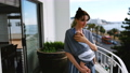 Young smiling mother standing in balcony with baby in sling 4k 66590398