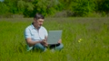 Businessman Works behind a Laptop Sitting on the Grass 66701533
