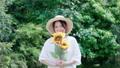 向日葵花的微笑的少婦在庭院裡 66737305