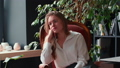 Lifestyle portrait of beautiful young blonde 20s business woman looking at camera smiling surprised on loft cafe chair. 66776776