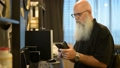 Mature bald bearded man using phone while working from home 66811052