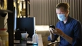 Young businessman with mask using hand sanitizer while working from home at night 66811065