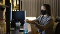 Young Asian woman with mask using hand sanitizer while working from home at night 66811066