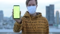 Face of young man with mask showing phone against view of the city 66811069