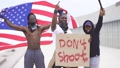 Group of young protesting male holding piece of cardboard with text - don't shoot 66830709