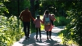 Young family of parents and two little kids walking in the summer park -mom and dad holding their daughter on rollers by hands 66861772