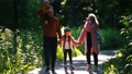 Happy family of parents and two little kids walking in the summer park -mom and dad holding their daughter on rollers by hands 66863685