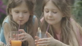 Close-up faces of beautiful Caucasian brunette girls with grey eyes drinking orange juice outdoors. Portrait of charming pretty twin sisters resting on backyard. Cinema FullHD ProRes HQ. 66954046