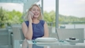 Portrait of positive adult Caucasian woman talking on the phone as sitting at restaurant table outdoors. Confident charming blond lady in blue dress resting in cafe on river bank. Lifestyle. 67108307