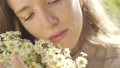 Young beautiful girl holds a bouquet of flowers of daisies in sunny weather, closeup view 67507926